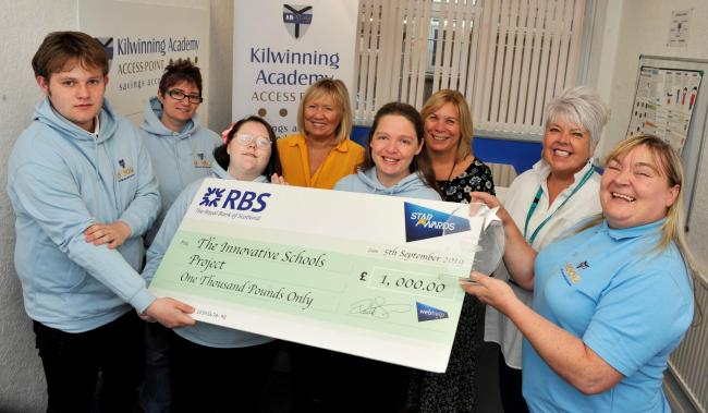 Janet Wells presents £1000 cheque to Kilwinning academy.